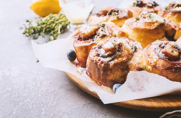 De délicieux petits pains à la cannelle faits maison avec du citron et des baies sur fond de bois