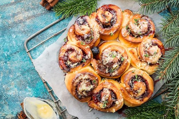 De délicieux petits pains à la cannelle faits maison avec du citron et des baies sur une surface bleue, vue du dessus