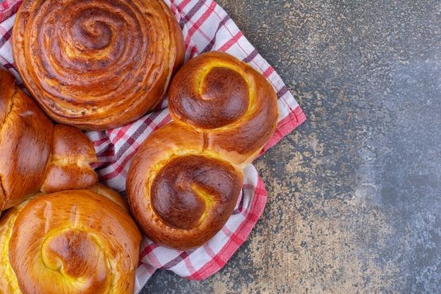 De délicieux petits pains emmitouflés sur une serviette froissée sur une surface en marbre