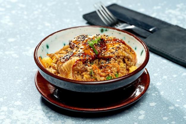 Délicieux plat pan-asiatique - riz au wok avec anguille, légumes et sauce aigre-douce dans un bol vert sur une surface grise