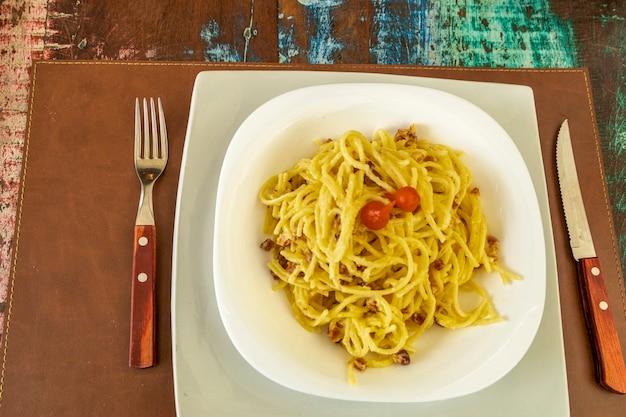 Délicieux plat de spaghettis à la carbonara sur table en bois