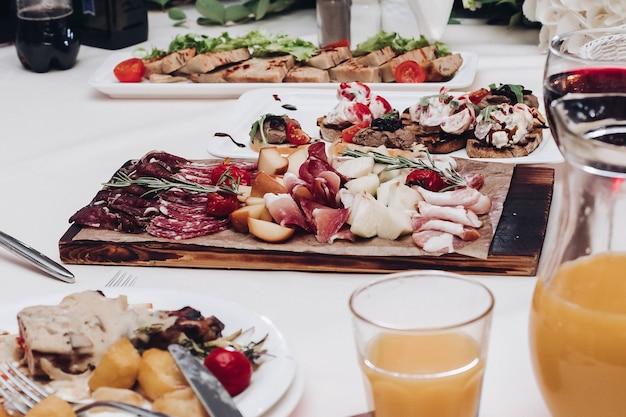 Délicieux plateau de viande froide sur table.vue sur la réception de mariage avec plateau de viande froide, jus de fruits et de baies et assiettes avec plat principal.