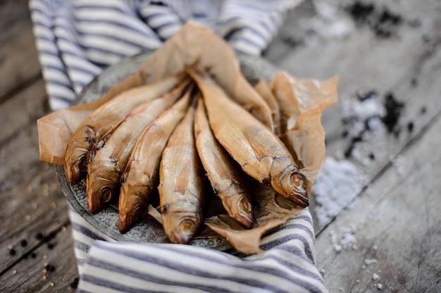 Délicieux poisson séché à la fumée sur une plaque sur un papier sulfurisé sur la serviette à rayures grises sur la table en bois