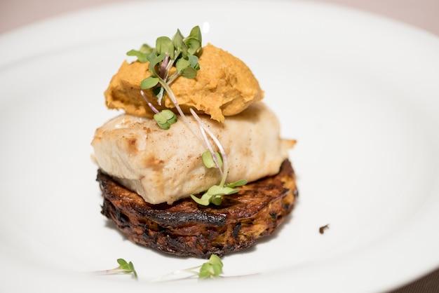 De délicieux poissons blancs servis sur des courgettes frites, avec une purée de patate douce et une sauce pourpre