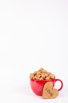 Délicieux pop-corn au caramel dans une tasse rouge et un cœur en bois