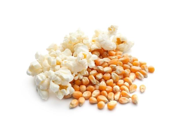 Délicieux pop-corn et grains sur blanc