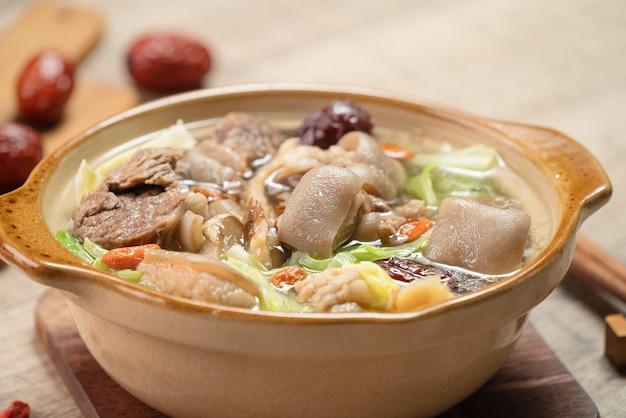 Délicieux pot chaud de mouton frais avec des légumes et des plantes médicinales chinoises comme la baie de goji et l'angélique chinoise dong quai