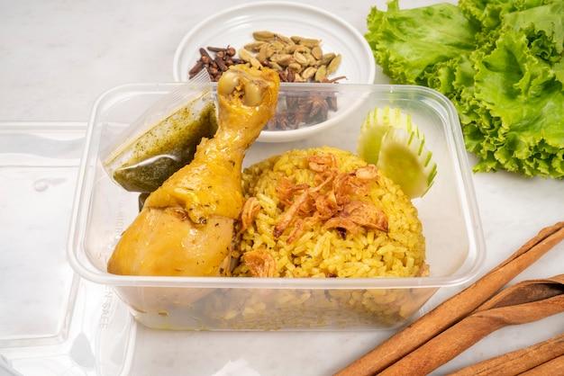 Délicieux poulet biryani épicé emballé dans un emballage en plastique, poulet biryani jaune riz au curry concept de livraison de nourriture.