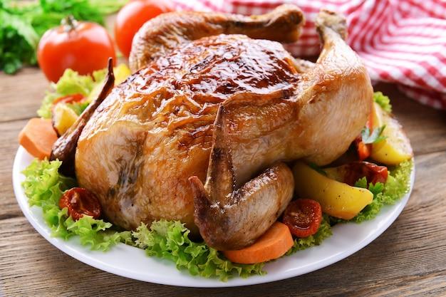 Délicieux poulet cuit sur plaque sur table close-up