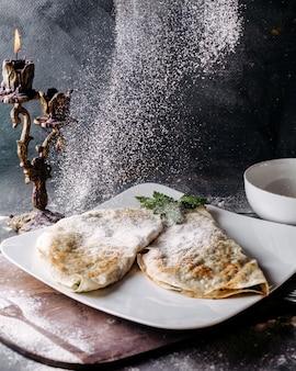 Délicieux qutabs célèbre repas oriental avec de la citrouille et de la viande à l'intérieur de la plaque blanche versée sur le sol gris
