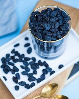 Délicieux raisins secs noirs dans un verre transparent sur un plateau blanc et une collation saine sur fond bleu