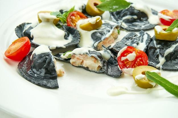 Délicieux raviolis à l'encre de seiche farcis aux crevettes et pétoncles, servis avec sauce blanche, tomates cerises et olives dans une assiette blanche sur nappe blanche
