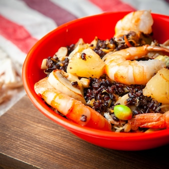 Un délicieux repas avec des crevettes dans une assiette rouge sur fond de bois vue en plongée.