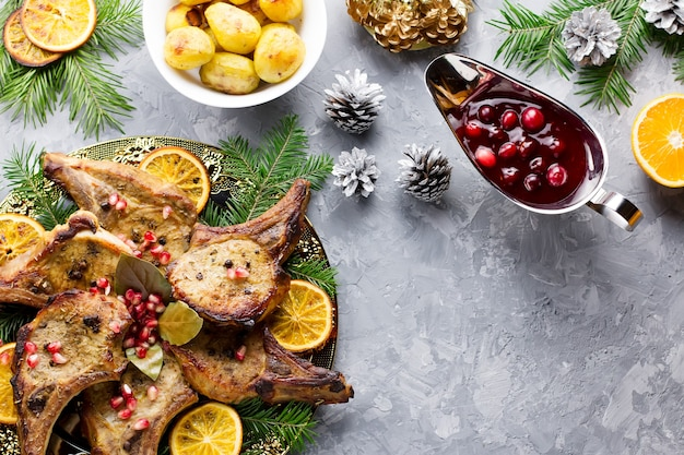 Délicieux repas de noël avec steak de viande rôtie, salade de couronne de noël, pomme de terre au four, légumes grillés, sauce aux canneberges.