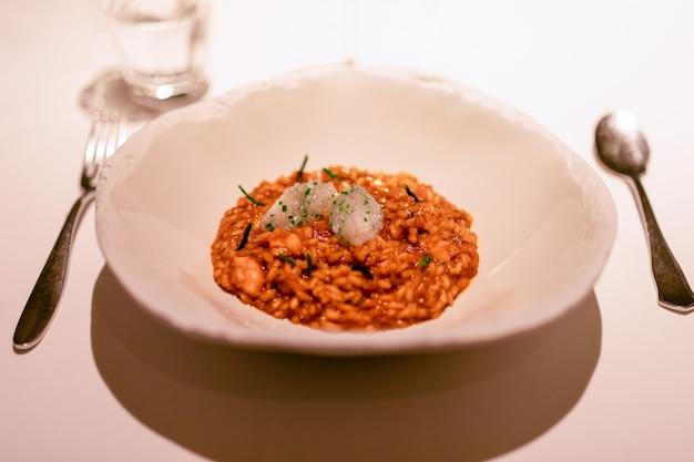 Délicieux risotto au caviar d'oursin, crevettes et tartare de calamars crus (selective focus)