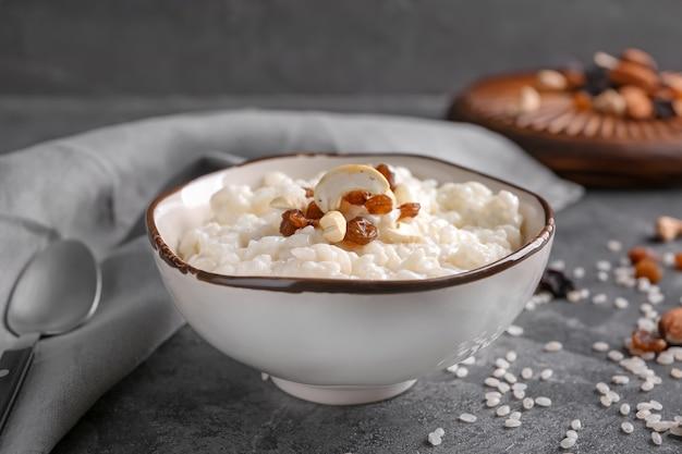 Délicieux riz au lait avec des noix et des raisins secs dans un bol sur table grise