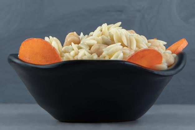 Délicieux riz aux pois chiches dans un bol noir.