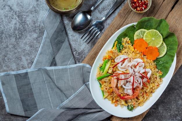 Délicieux riz frit aux fruits de mer avec crevettes, œufs et oignons de printemps avec soupe.