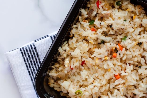 Délicieux riz frit dans une boîte à lunch avec napery sur fond de marbre