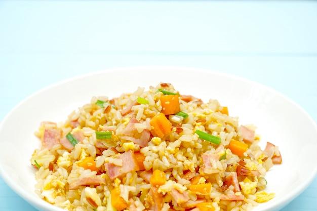 Délicieux riz frit avec jambon, oeuf, carotte et oignon sur une plaque blanche