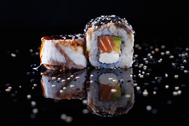 Délicieux rouleau de sushi avec poisson et sésame arrosés de sauce soja sur fond noir avec reflet