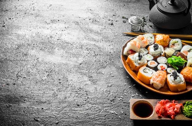 De délicieux rouleaux de sushi aux crevettes, légumes et saumon sur une assiette en bois. sur fond rustique noir