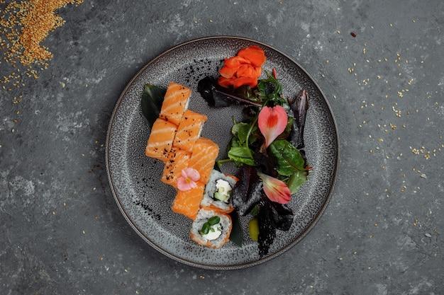 De délicieux rouleaux de sushi frais avec du saumon et du fromage de philadelphie sur plaque grise sur fond de pierre sombre