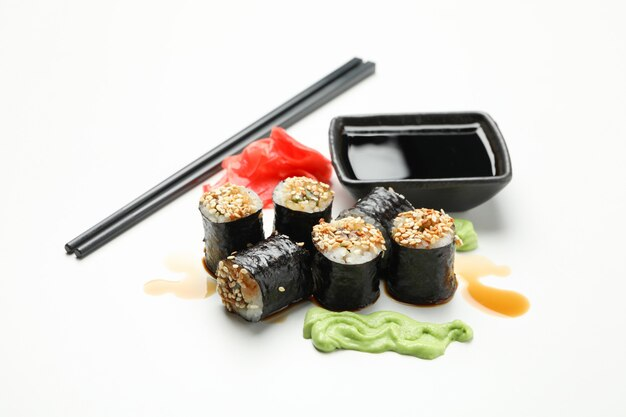 Délicieux rouleaux de sushi, sauces et baguettes sur une surface blanche