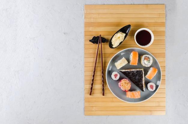 Délicieux rouleaux de sushi sertis de sauces, baguettes, gingembre sur table. service de livraison cuisine japonaise
