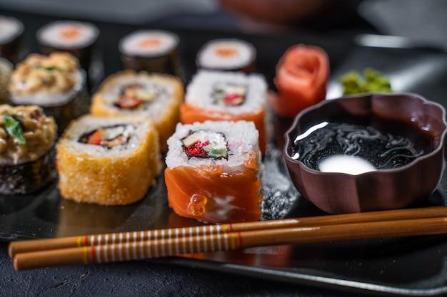 De délicieux rouleaux de sushi servis sur un tableau noir avec des baguettes