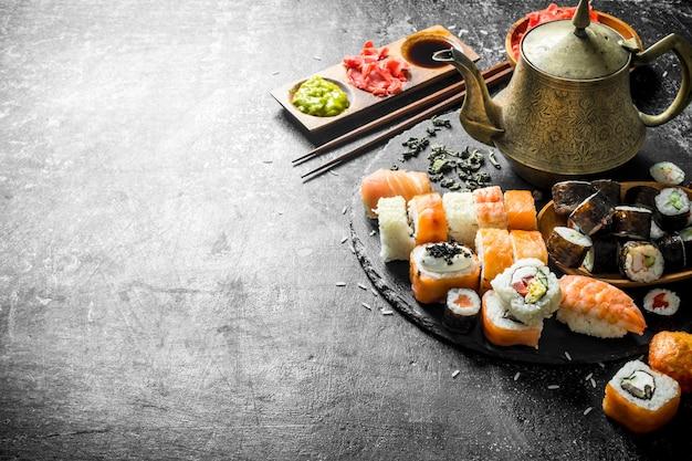 Délicieux rouleaux de sushi et thé vert parfumé. sur table rustique sombre