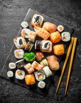 Délicieux rouleaux, sushis et makis sur une planche de pierre avec des baguettes. sur fond rustique noir