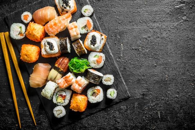 Délicieux rouleaux, sushis et makis sur une planche de pierre avec des baguettes. sur une surface rustique noire
