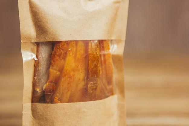 Délicieux saccadé sur un fond en bois. produits dans des emballages artisanaux. collation pour l'alcool. photo macro. fermer.