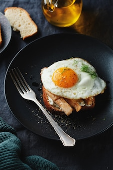 Délicieux sandwich appétissant avec des morceaux de poulet et œuf frit servi sur une assiette sur une surface sombre
