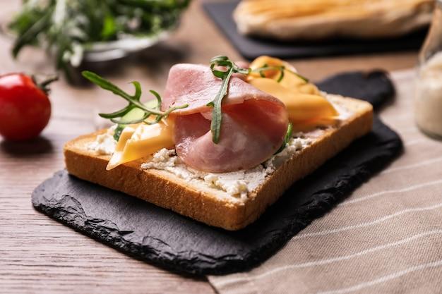 Délicieux sandwich au jambon sur table en bois, gros plan