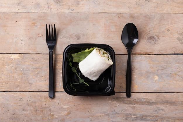 Délicieux sandwich au wrap frais avec du poulet et des légumes dans une boîte noire sur une table en bois, vue du dessus