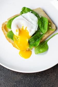 Délicieux sandwich aux œufs pochés aux épinards sur la table