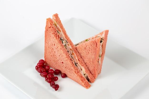 Délicieux sandwich avec du pain rose sur une assiette blanche