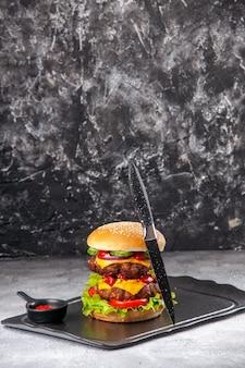 Délicieux sandwich fait maison et ketchup à la fourchette sur plateau noir sur une surface isolée en détresse grise
