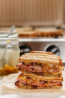 Délicieux sandwich à la viande, oignons frits, fromage et moutarde