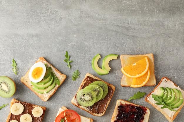 Délicieux sandwichs assortis sur fond gris, vue de dessus