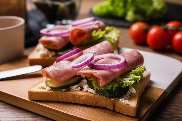 Délicieux sandwichs au jambon sur table en bois, gros plan