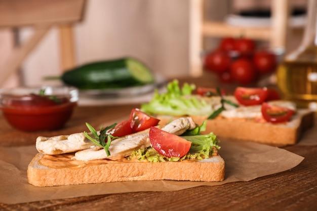 Délicieux sandwichs au poulet sur table en bois
