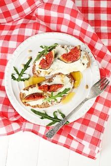 Délicieux sandwichs aux figues sucrées et fromage cottage sur assiette