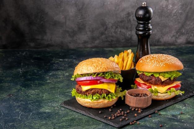 De délicieux sandwichs faits maison sur une planche à découper noire frites du poivre sur une surface floue gris foncé