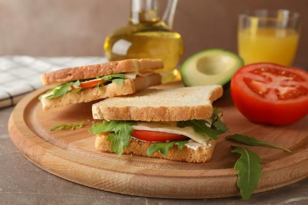 Délicieux sandwichs, huile, avocat, jus et tomate sur planche de bois, close up