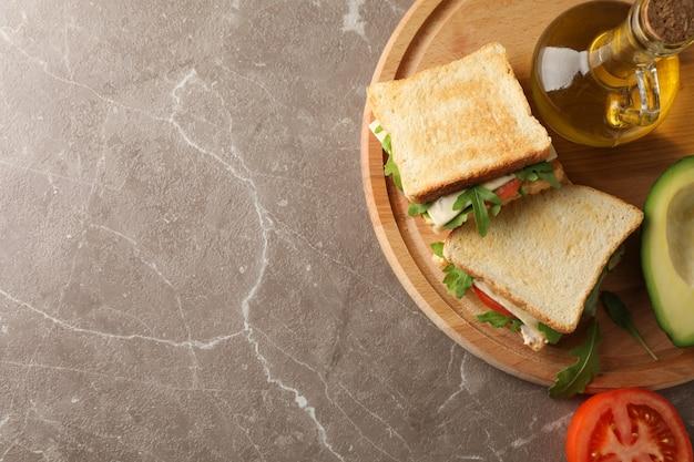 Délicieux sandwichs, huile, avocat et tomate sur fond gris, espace pour le texte