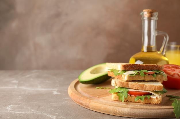 Délicieux sandwichs, huile, avocat et tomate sur table grise, espace pour le texte