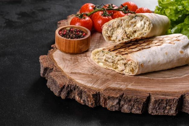 Délicieux shawarma frais avec de la viande et des légumes sur une table en béton foncé. restauration rapide, cuisine turque